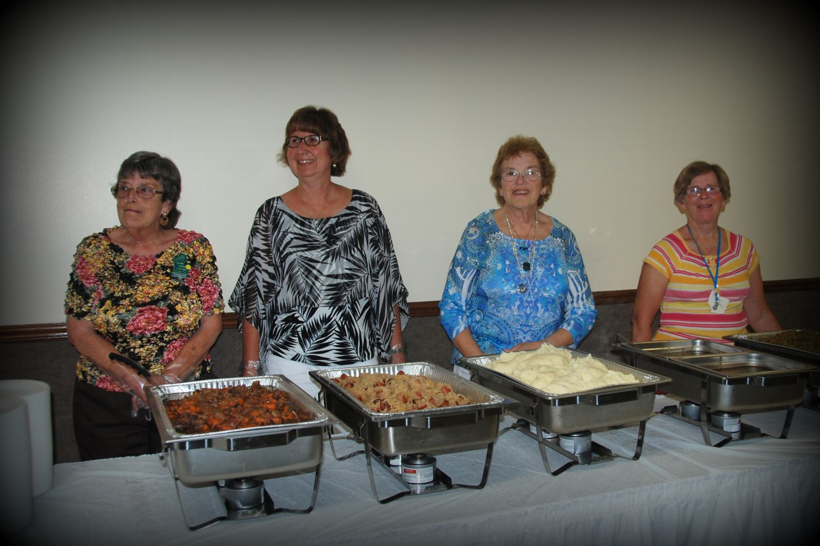 Members of both clubs serving the Saturday night dinner